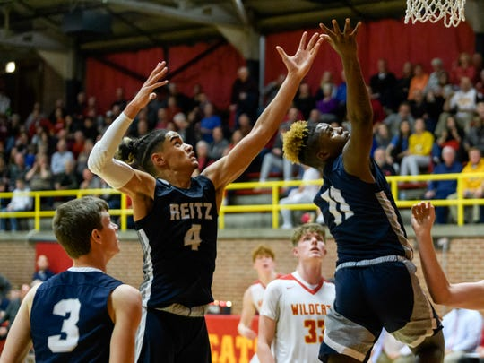 Reitz's Khristian Lander (4) and Reitz's Mar'Quon Givens (11) prepare to catch the rebound during the third quarter against the Mater Dei Wildcats at Mater Dei High School in Evansville, Ind., Friday, Dec. 13, 2019. The Panthers made a huge comeback in the fourth quarter to defeat the Wildcats, 79-73.