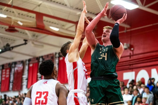 Iowa City West guard Even Brauns (34) makes a basket as Iowa City High's Kolby Kucera, center, and Keshawn Christian (23) defend during a Class 4A high school boys' varsity basketball game, Friday, Dec. 13, 2019, at City High School, in Iowa City, Iowa.