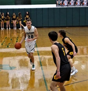 Fisher Catholic's Bryson Vogel brings the ball up the court against Berne Union's Chase McCartney. Vogel scored 16 points to help lead the Irish to a 40-34 victory.