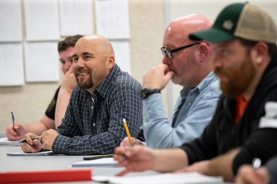 Christopher Jackson, left, a former AK Steel employee, looks on during class in the Braidy Industries training wing in the Ashland Community and Technical College in Ashland, Kentucky. Jackson worked for AK Steel for 11 years before signing up for Braidy's training program.
