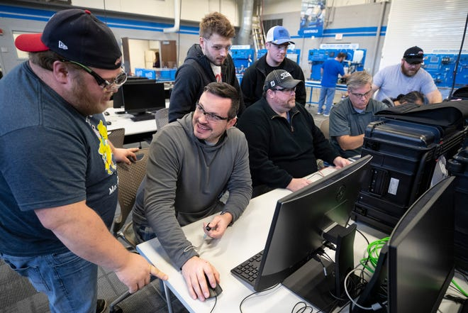 Joseph Marcum, second from left, talks with students as they work in the Braidy Industries training area in the Ashland Community and Technical College in Ashland, Kentucky, on Nov. 26, 2019.