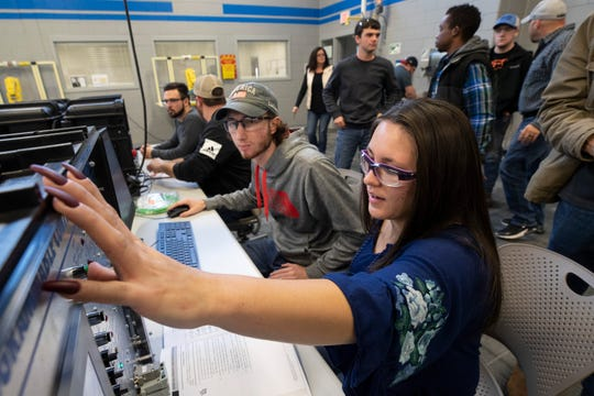 Hollyann Miller, from right, and Blake Stevens work on equipment in the Braidy Industries training area in the Ashland Community and Technical College in Ashland, Kentucky.