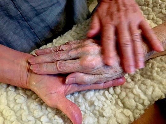 In this 2016 photo provided by Thomas Marrinson, Allison Beach holds the hand of her ailing mother Kathryne Beach inside her home in Hinesburg, Vt. For the first time since the early 1900s, more Americans are dying at home rather than in hospitals, a trend that reflects more hospice care and progress toward the kind of end that most people say they want.