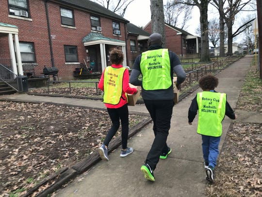 """Cecilia, Abe and Eli Mbow walk through Nashville's Cheatham Place neighborhood delivering holiday food boxes on Saturday, Dec. 14, 2019. Through the """"Feed the Need"""" project, a partnership between the Rotary Club of Nashville and Second Harvest Food Bank of Middle Tennessee, nearly 2,000 families received fresh and canned foods."""
