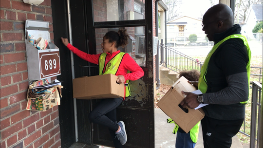 """Cecilia Mbow, a 13-year-old student at Harpeth Hall, knocks on a door in Nashville's Cheatham Place neighborhood to deliver holiday food boxes with her dad, Abe, and brother, Eli, on Saturday, Dec. 14, 2019. Through the annual """"Feed the Need"""" project, a partnership between the Rotary Club of Nashville and Second Harvest Food Bank of Middle Tennessee, nearly 2,000 families received fresh and canned foods."""