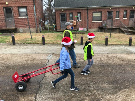 """Morgan Burns, 9, walks through Nashville's Cheatham Place neighborhood after delivering several holiday food boxes with her dad, Ben, and her twin brother, Anderson, on Saturday, Dec. 14, 2019. Through the annual """"Feed the Need"""" project, a partnership between the Rotary Club of Nashville and Second Harvest Food Bank of Middle Tennessee, nearly 2,000 families received fresh and canned foods."""