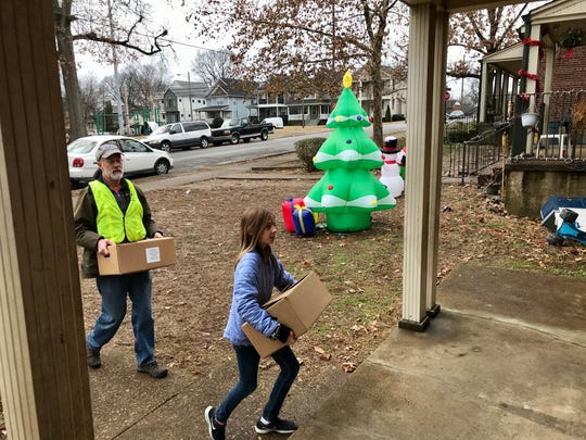 """Morgan Burns, 9, walks onto a front porch in Nashville's Cheatham Place neighborhood to deliver holiday food boxes with her dad, Ben, on Saturday, Dec. 14, 2019. Through the annual """"Feed the Need"""" project, a partnership between the Rotary Club of Nashville and Second Harvest Food Bank of Middle Tennessee, nearly 2,000 families received fresh and canned foods."""