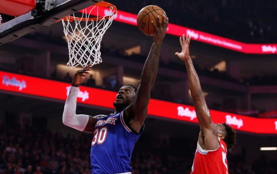 New York Knicks forward Julius Randle, left, goes to the basket past Sacramento Kings guard Buddy Hield during the first quarter of an NBA basketball game in Sacramento, Calif., Friday, Dec. 13, 2019.