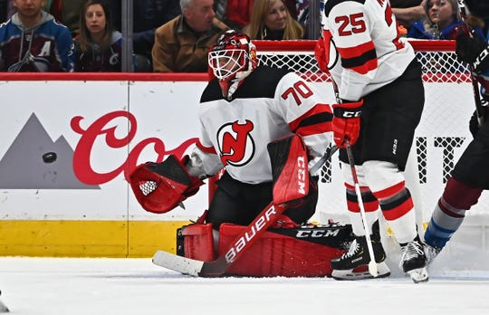 Dec 13, 2019; Denver, CO, USA; New Jersey Devils goaltender Louis Domingue (70) prepares to glove a puck in the first period against the Colorado Avalanche at the Pepsi Center.