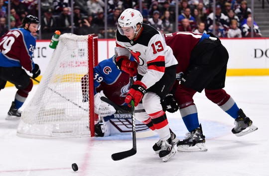 Dec 13, 2019; Denver, CO, USA; New Jersey Devils center Nico Hischier (13) controls the puck in front of the Colorado Avalanche net in the first period at the Pepsi Center.