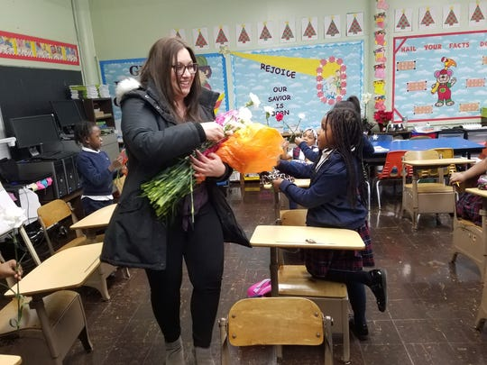 Members of Rising Tide, a Jersey City-based non-profit, handed out carnations to students at Sacred Heart School in the wake of the deadly shooting on Dec. 10, 2019. Amelia Ramos' classroom was only 10-feet from the U-Haul van and right across the street from the market where the shooting took place.