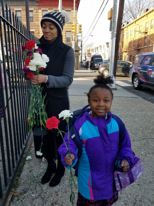 Blare Davenport, Grade 1, smiled as she received a carnation from members of Rising Tide, a Jersey City-based non-profit, at Sacred Heart School in the wake of the deadly shooting on Dec. 10, 2019. Teacher Delos Reyes helped hand them out to students as well.