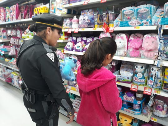 New Mexico State Police Patrolman Angie Ortega shops with Lizeth Marroquin at Walmart during the Shop with a Cop event on Saturday, Dec. 14, 2019.