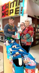 U. S. Marine Corps veteran Tim White receives a Christmas gift bag from Daughters of the American Revolution member Faith Morley at the Mesilla Valley Community of Hope. Kat McClure, center, is the  veteran services coordinator at the Community of Hope.