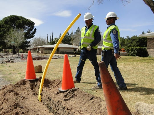 Workers install new yellow poly service lines that will bring natural gas to homes in a Las Cruces neighborhood.