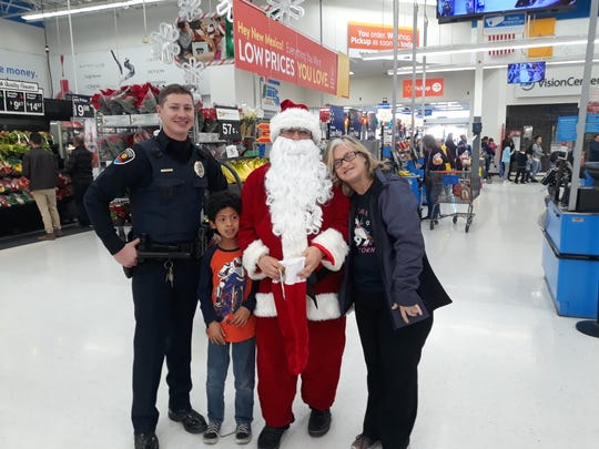 (L-R) Ofc. John Guaderrama of the Las Cruces Police Department, Deyshawn Smith, Santa Claus and Jennifer Schell pose for a photo during the Shop with a Cop event at Walmart on Saturday, Dec. 14, 2019.