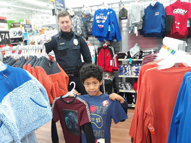 Ofc. John Guaderrama of the Las Cruces Police Department helps Deyshawn Smith pick out some new shirts during the Shop with a Cop event on Saturday, Dec. 14, 2019.