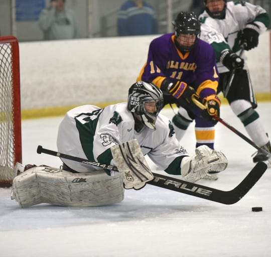 Novi High goalie Luis Lettmann smothers up a shot on net during the team's Dec. 14 game against Warren DeLaSalle.
