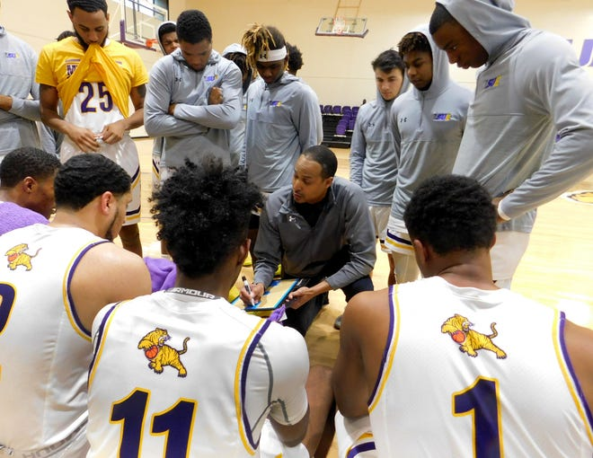 LSU-Eunice men's basketball coach Byron Starks diagrams a play as his team gathers around during a timeout of a recent game. Starks, a former UL basketball standout, has the Bengals 9-3 in their second season.