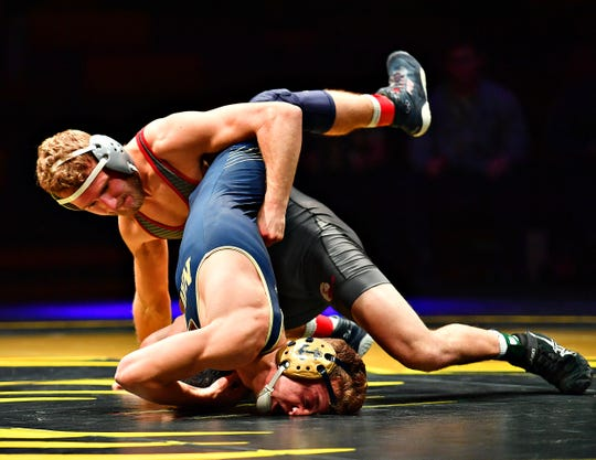 Lock Haven's Kyle Shoop, back, and Navy's Cody Trybus wrestle in the 141 pound weight class during Rumble in the Jungle II in Fitzkee Event Center at Red Lion Area High School in Red Lion, Friday, Dec. 13, 2019. Dawn J. Sagert photo