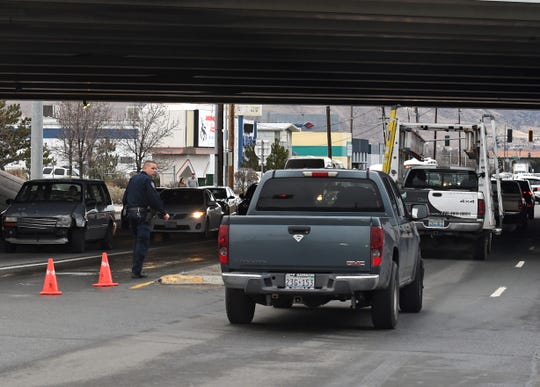 A Reno police officer directs traffic under the I-580 at the Mill Street onramp during an acid spill on the freeway on Friday afternoon, Dec. 13, 2019.