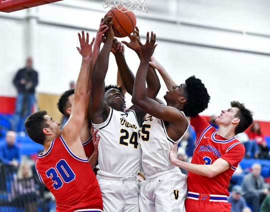 Victor's C.J. James (24) and Phil Nwugwo reach for a rebound between Fairport's Stefan Milinkovic, left, and Max Molisani during a regular season game at Fairport High School, Friday, Dec. 13, 2019. Victor beat Fairport 50-43 in overtime.