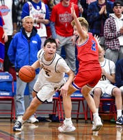 Victor's Matt Caggiano, left, drives the baseline against Fairport's Jack Lindstrom during a regular season game at Fairport High School, Friday, Dec. 13, 2019. Victor beat Fairport 50-43 in overtime.