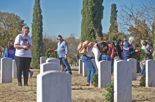People attending a ceremony at Belvedere Memorial Park lay wreaths beside the graves of veterans Saturday, Dec. 14, 2019 in San Angelo. The program is part of the nationwide Wreaths Across America event.