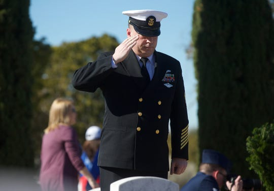 Navy Master Chief Joe Reynolds salutes the grave of a veteran after laying down a wreath during a ceremony at Belvedere Memorial Park in San Angelo on Saturday, Dec. 14, 2019. The program is part of the nationwide Wreaths Across America event.