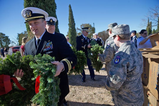 People gather wreaths to lay beside the graves of veterans at Belvedere Memorial Park on Saturday, Dec. 14, 2019.