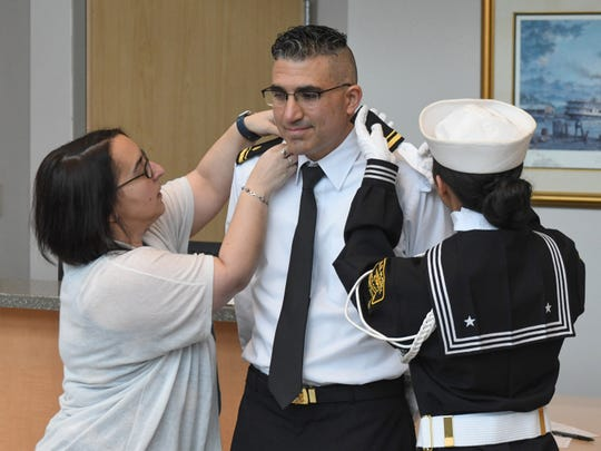 Beth DiPasqua, wife of Lt. Christopher DiPasqua, center, and Sea Cadet PO3 Zoey DiPasqua, daughter, fixes his uniform after being commissioned during a ceremony Saturday, Dec. 14, 2019, at Peninsula Regional Medical Center in Salisbury.