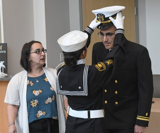 Sea Cadet PO3 Zoey DiPasqua, daughter, puts the hat on Lt. j.g. Christopher DiPasqua after being commissioned, as his wife, Beth DiPasqua watches Saturday, Dec. 14, 2019, at Peninsula Regional Medical Center in Salisbury.