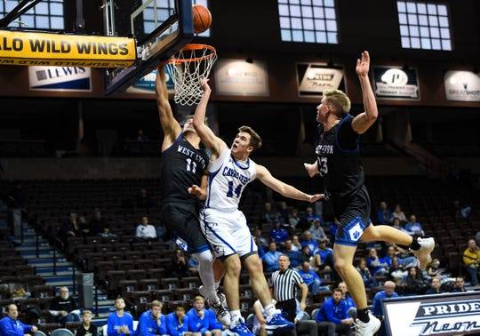 Grant Huber of St. Thomas More has the ball knocked from his hand by Riley Hoogeveen of West Lyon during the Barefoot Classic on Saturday, Dec. 14, at the Sanford Pentagon in Sioux Falls.