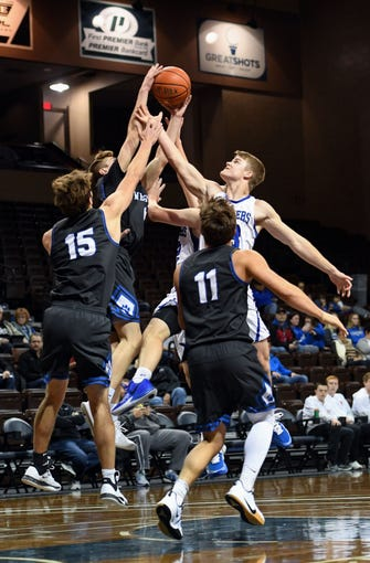 Charlie Larson of St. Thomas More goes up for a rebound against several West Lyon players during the Barefoot Classic on Saturday, Dec. 14, at the Sanford Pentagon in Sioux Falls.