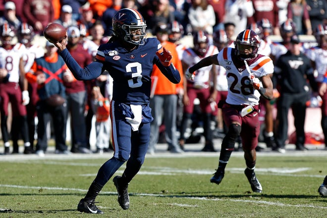 Virginia Cavaliers quarterback Bryce Perkins (3) passes the ball as Virginia Tech Hokies defensive back Jermaine Waller (28) chases in the first quarter at Scott Stadium.