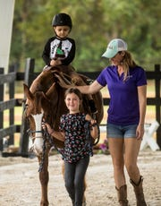 Isaac Merced,5, rides Major Moves at Southern Ambitions Ranch in North Fort Myers on Saturday Dec. 14, 2019. The ranch hosted a Holiday party for children with cancer. Isaac is being treated for Leukemia. The party was sponsored by 21st Century Oncology and featured a sitting with Santa, pony and horse rides among other things. Leading Major Moves is her owner, Audrey Price, 6, and her mother, Lauren Price who were helping with the event.