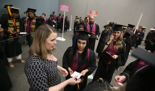 "Ann Arnold-Ogden works with students to make sure she knows how to pronounce each one before graduation ceremonies for Midwestern State University, Dec. 14, 2019 at the Kay Yeager Coliseum. ""This isn't hard,"" Arnold-Ogden said. ""This is fun. There's nothing hard about it."" She has been annoouncing the names at graduation for about six year, she recalled. Photo by Bradley Wilson"
