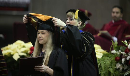 Jessica Carr receives her master's hood from Kathryn Zuckweiler, dean of the graduate school. Carr got her Master of Science in Nursing at graduation ceremonies for Midwestern State University, Dec. 14, 2019 at the Kay Yeager Coliseum. Photo by Bradley Wilson