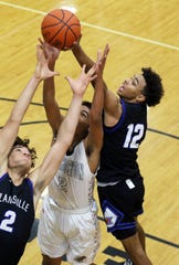 Zanesville's Jalen Moeller-Kile (2) and Isaac Mayle reach for a rebound with Coshocton's Tyren Walker Friday night in Coshocton.