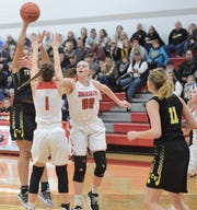 Tri-Valley's Kyndal Howe makes a pass to Riley Tracy (11), while being guarded by Sheridan's Aubrie White (1) and Faith Stinson (00) on Saturday, as the Scotties won 41-33.