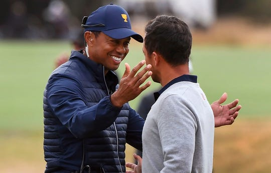 U.S. team captain Tiger Woods embraces Xander Schauffele after Schauffele and teammate Patrick Cantlay won their match during the third day of the Presidents Cup golf tournament in Melbourne on December 14, 2019. (Photo: William West, AFP)