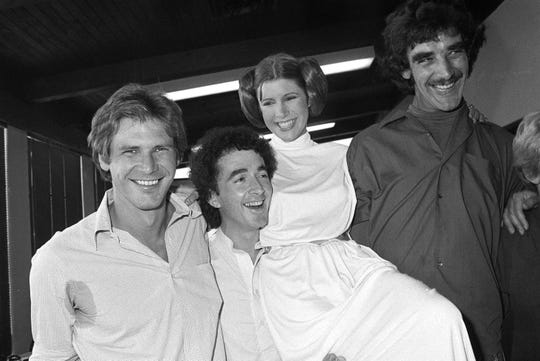 """Original """"Star Wars"""" stars Harrison Ford (far left), Anthony Daniels, Carrie Fisher and Peter Mayhew take a break while filming a holiday TV special in 1978."""