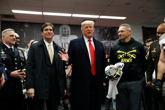 President Donald Trump speaks with members of the Army team in Philadelphia Saturday before the Army-Navy college football game.