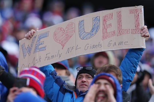 A fan holds a sign for New York Giants quarterback Eli Manning (10) during the first quarter against the Miami Dolphins at MetLife Stadium.