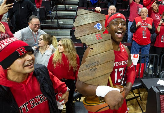 Rutgers Shaq Carter carries the Garden State Hardwood trophy around after the game. Seton Hall Basketball at Rutgers in Piscataway, NJ on 12/12/19.