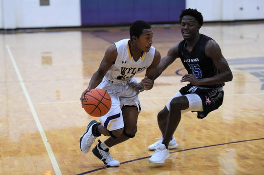 Wylie's Jahzair George (2) drives against Midland Christian's Tre Hubert (15) during the Catclaw Classic finale at Bulldog Gym on Saturday. The Bulldogs fought before falling 47-43.