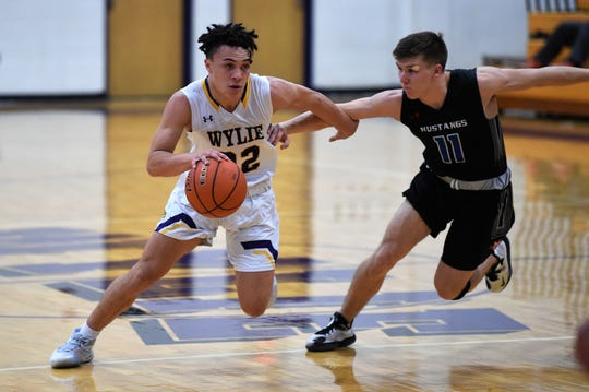Wylie's Shayden Payne (22) drives against Midland Christian's Mitch McCann (11) during the Catclaw Classic finale. Payne has turned into the Bulldogs' leading scorer in the last three games as they have been without several key pieces due to injuries.