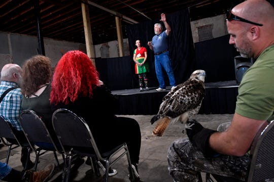 Tony Lyons holds Granite, a Krider's red-tailed hawk, as Mark Runnells gives a presentation on falconry Saturday at the Lyric Theatre in Eastland. The Ryan Vance Memorial Falconry meet was held over the weekend.