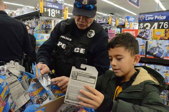 Victor Pierce of the Emmett Township Department of Public Safety and Kalan Matson-El-Khaimy, 8,  search for the right Hot Wheels.
