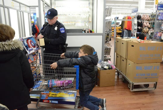 Lance Gordan-Badillo, 9, of Battle Creek, waits on the end of the cart as Officer Chris Martin of Kellogg Community College adds the total of the purchases.